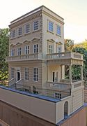 Regency dolls house showing side portico with french doors to Dining Room and wine cellar.