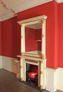 Regency dolls house with oriental fireplace and overmantel and hobgrate with glowing coals.